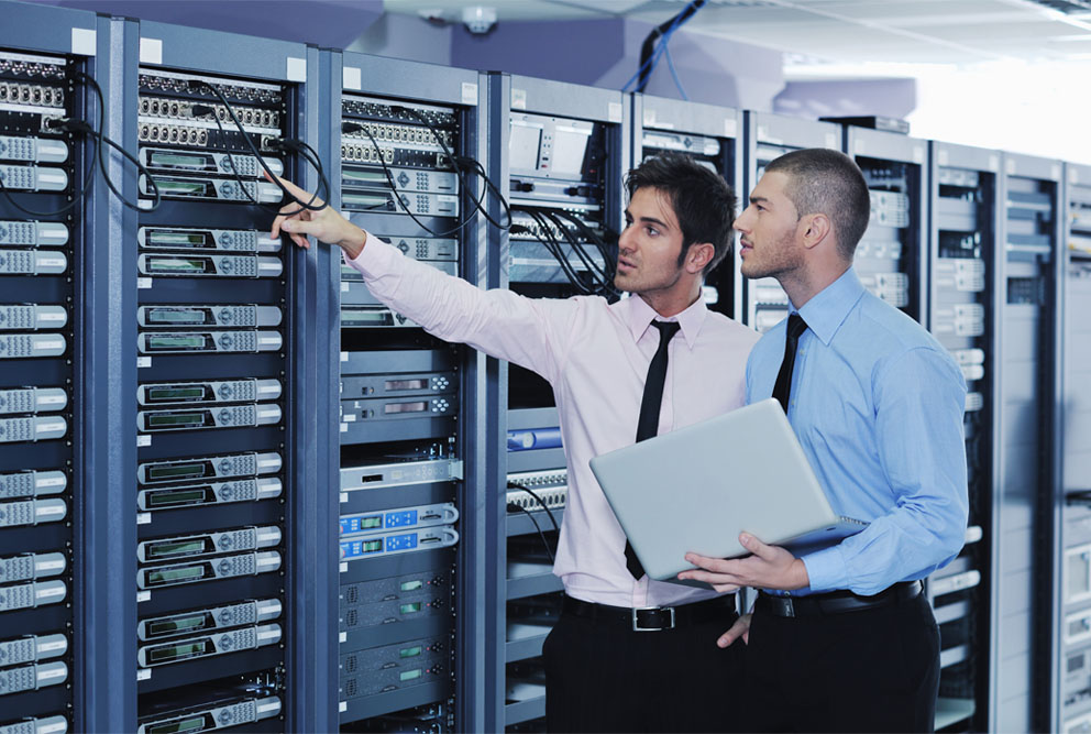 Two members of the managed document solutions team inspecting a computer server